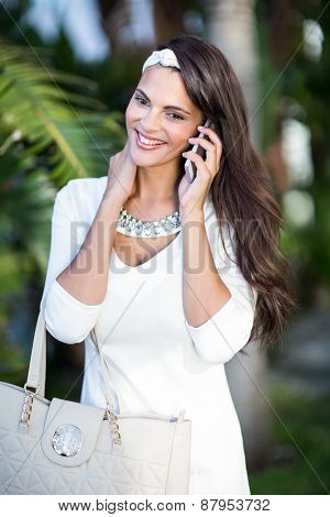 Beautiful brunette on the phone outside