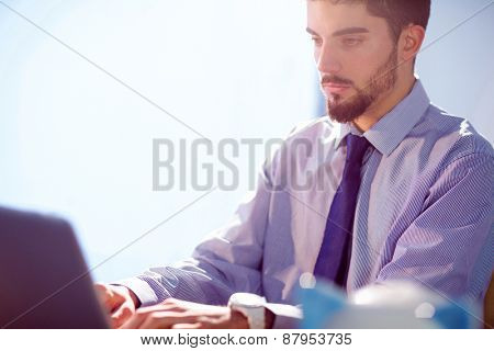 Businessman using laptop at deskshot in studio