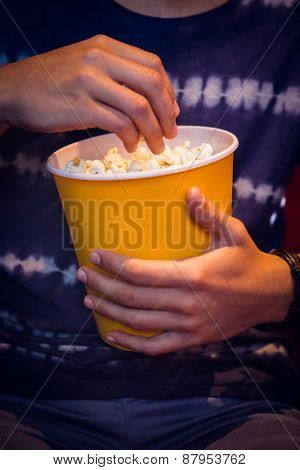 Young man watching a film and eating pop corn at the cinema