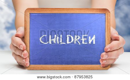 The word children and hands showing chalkboard against bright blue sky with clouds