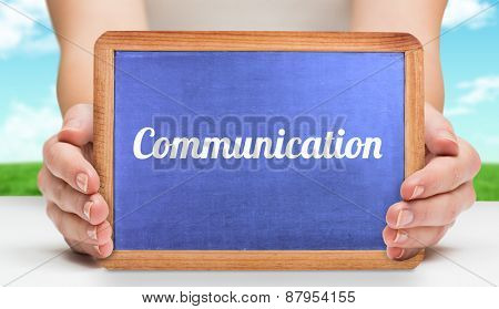 The word communication and hands showing chalkboard against field and sky