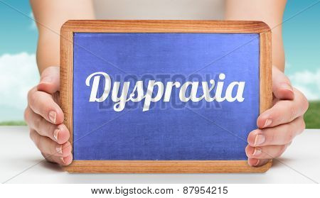 The word dyspraxia and hands showing chalkboard against field and sky
