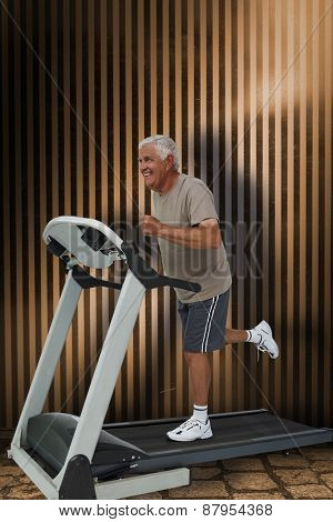 Full length of a senior man running on a treadmill against dark grey room