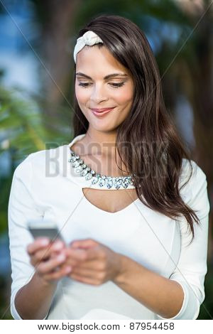 Beautiful brunette using her smartphone outside