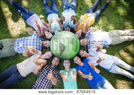 Silver earth against happy friends in the park lying in circle