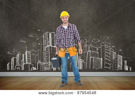 Happy male hanyman carrying toolbox against room with wooden floor