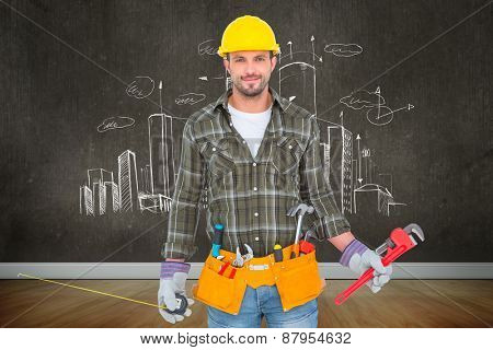 Manual worker holding various tools against room with wooden floor