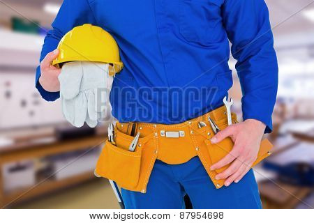 Handyman holding helmet against workshop