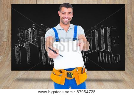 Smiling handyman giving clipboard for signature against composite image of black card