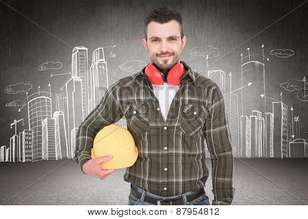 Handyman with earmuffs holding helmet against hand drawn city plan