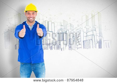 Portrait of happy manual worker gesturing thumbs up against grey