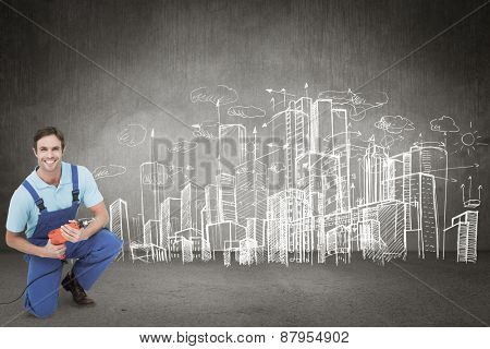 Happy carpenter holding drill machine against hand drawn city plan