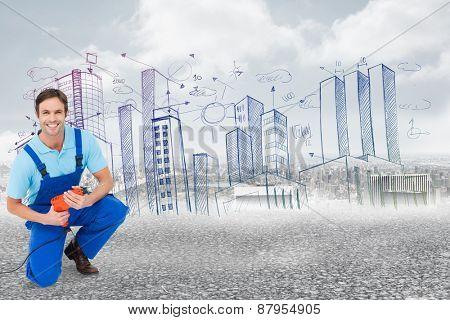 Happy carpenter holding drill machine against black road