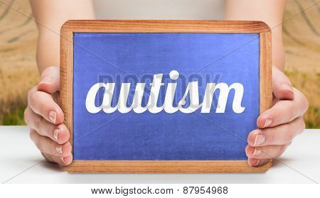The word autism and hands showing chalkboard against rural fields