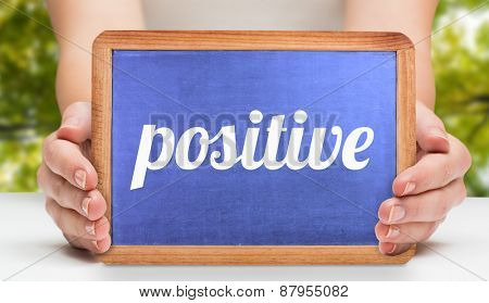 The word positive and hands showing chalkboard against low angle view of tall trees