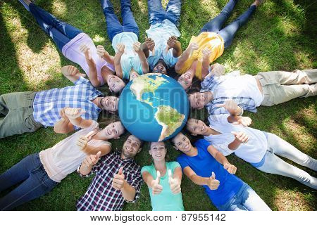Earth against happy friends in the park lying in circle