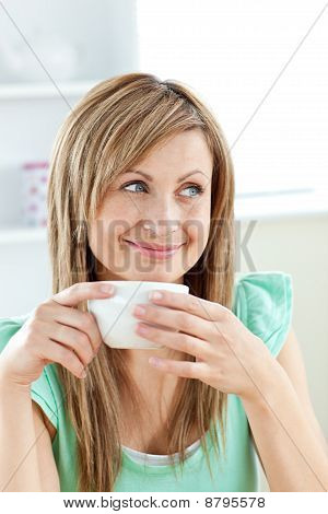Smiling Woman Holding A Cup Of Coffee In The Kitchen