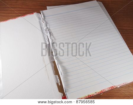 Opened And Torn Notebook On Wood Background