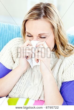Diseased Woman Lying On A Sofa With Tissues And Blowing