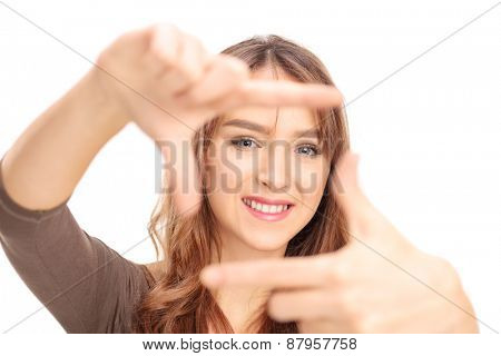 Beautiful brunette girl framing a photo with her fingers with the focus on her face isolated on white background