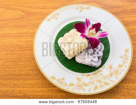 Yellow And Black Carved Mochi Cake On Thai Banana Leaf In A White Gold Pattern Plate