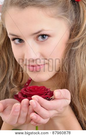 Close-up Portrait Of A Beautiful Teenage Girl Smelling A Rose