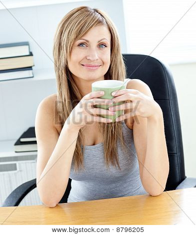 Glowing Businesswoman Holding A Cup At Her Desk