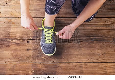 Young runner tying her shoes