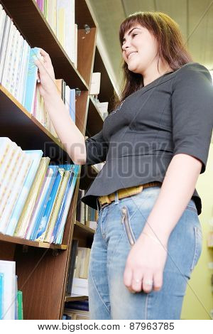 Beautiful Woman in the library takes the book from the shelf