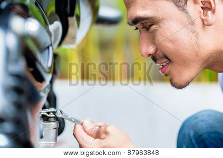 Close up of Asian man maintaining motorcycle