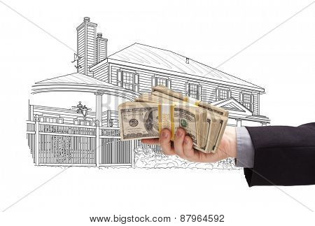 Hand Holding Thousands of Dollars In Cash Over House Drawing.