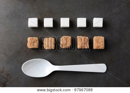 High angle view of white and brown sugar cubes and a white plastic spoon on a metal baking sheet. Five cubes of both the white and brown lumps line up in rows. Horizontal format.