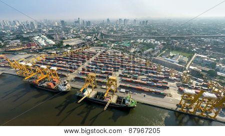 Aerial Image Of Cargo Ships At Seaport With City View