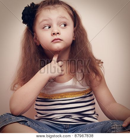 Thinking Prying Kid Girl Sitting In Jeans With Finger Under Face