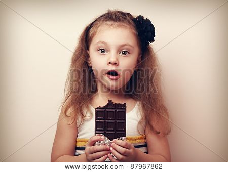 Surprising Kid Girl Looking With Big Eyes And Holding Chocolate