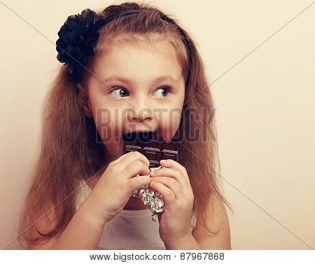 Fun Surprised Kid Girl Biting Dark Chocolate. Vintage Closeup