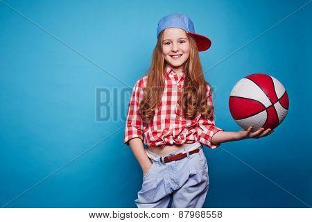Cute girl with basketball looking at camera