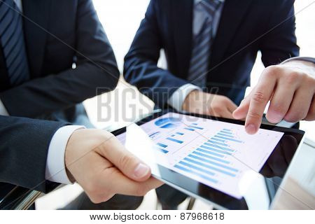 Business document in touchpad and hands of male employees during discussion of data