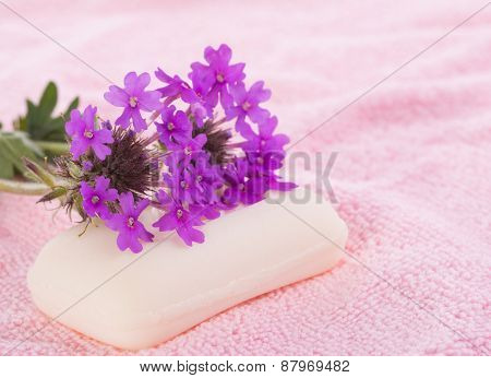 Soap on light pink wash cloth, with purple wildflowers on top