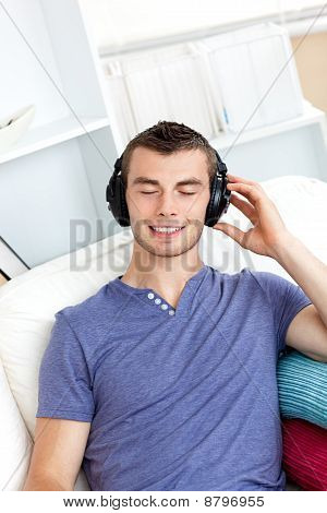 Relaxed Young Man Listening To Music Sitting On The Couch In The Living-room