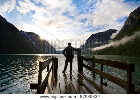 Silhouette of man looking on lake