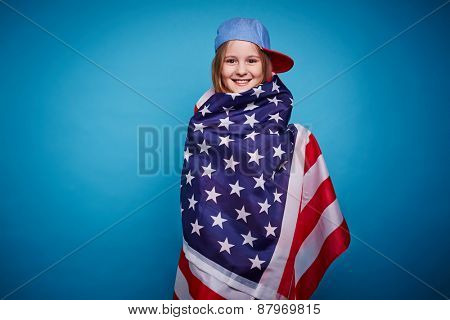 Cute girl wrapped up in USA flag looking at camera