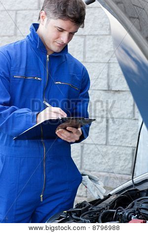 Handsome Mechanic Writing On A Clipboard Standing In Front Of A Car