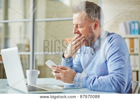 Tired businessman with cellphone yawning at workplace