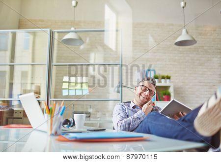 Cheerful man using modern technologies in office