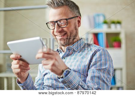Happy man in eyeglasses using digital tablet