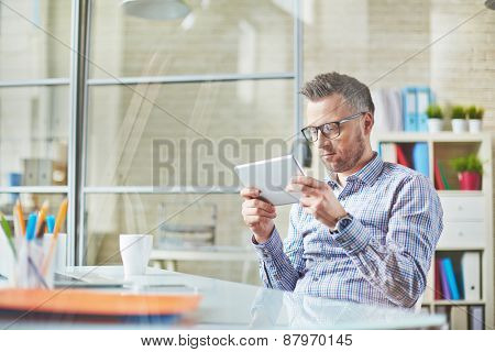 Handsome businessman with digital tablet working in office