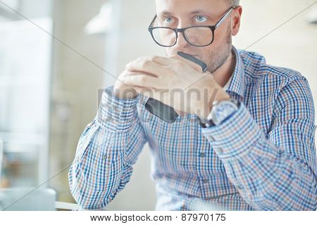 Serious businessman in eyeglasses holding cellphone