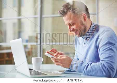 Happy manager writing sms in office