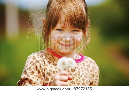 Little girl with dandelion outdoors